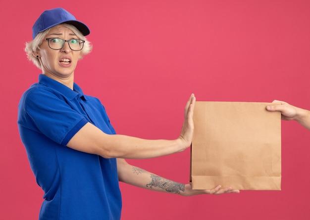 파란색 제복을 입은 젊은 배달 여자와 분홍색 벽 위에 서서 혼란스럽고 걱정되는 종이 패키지를 거부하는 모자