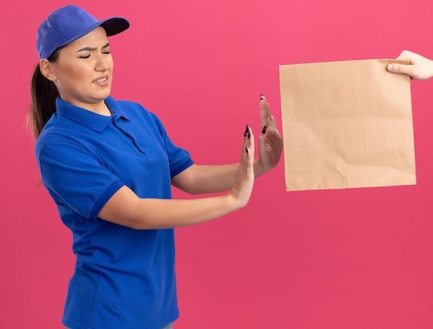 파란색 제복을 입은 젊은 배달 여자와 분홍색 벽 위에 서있는 종이 패키지를 거부하는 모자