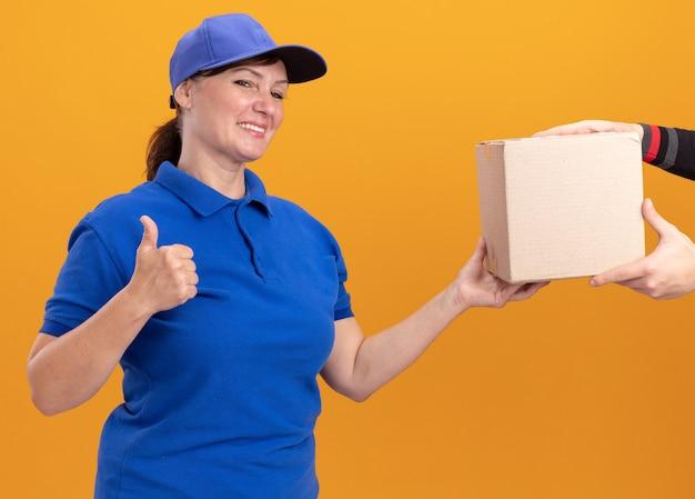 オレンジ色の壁の上に立っているボックスパッケージを受け取っている間、青い制服とキャップの笑顔の若い配達の女性は、okサインを示しています