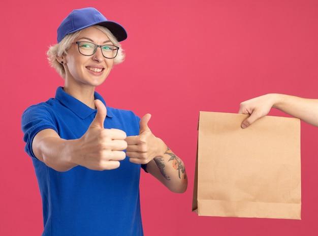 ピンクの壁の上に立っている紙のパッケージを受け取っている間、青い制服とキャップの笑顔の若い配達の女性は親指を立てて