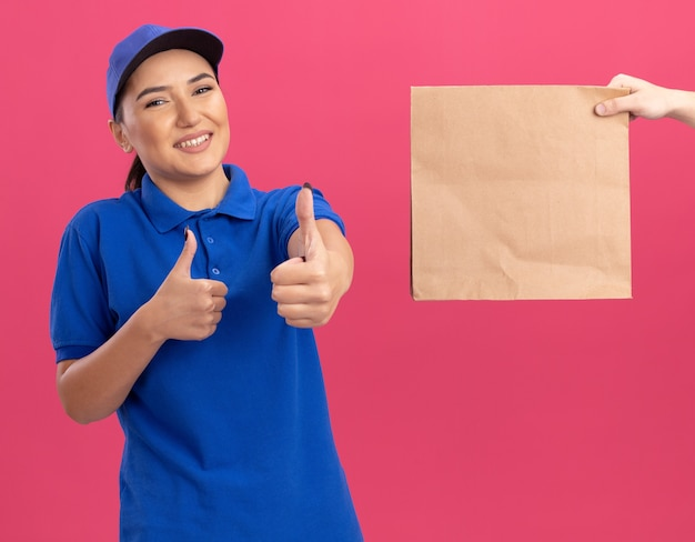 ピンクの壁の上に立っている紙のパッケージを受け取っている間、青い制服とキャップの笑顔の若い配達の女性は親指を上に表示します