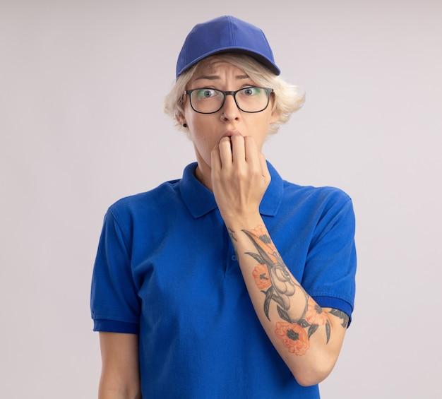 青い制服とキャップストレスと白い壁の上に立っている神経質な噛む爪の若い出産女性