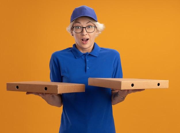 Молодая женщина-доставщик в синей форме и кепке в очках держит коробки для пиццы, изумленные и удивленные над оранжевой стеной