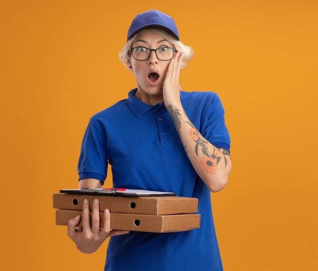 Молодая женщина-доставщик в синей форме и кепке в очках, держащая коробки для пиццы и буфер обмена, изумленная и удивленная над оранжевой стеной