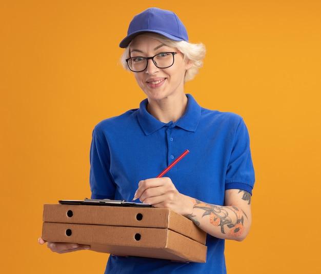 Молодая женщина-доставщик в синей форме и кепке в очках держит коробки для пиццы и буфер обмена с пустыми страницами, что-то пишет карандашом, улыбаясь над оранжевой стеной