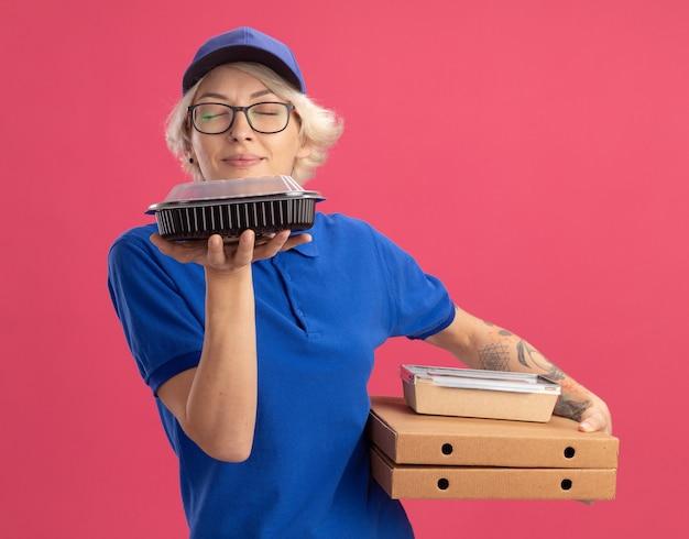 Молодая женщина-доставщик в синей форме и кепке в очках держит коробки для пиццы и продуктовые пакеты, вдыхая приятный аромат над розовой стеной