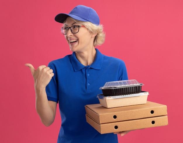 Молодая женщина-доставщик в синей форме и кепке в очках держит коробки для пиццы и продуктовые пакеты, весело улыбаясь, указывая указательным пальцем в сторону над розовой стеной