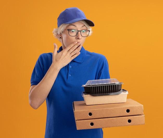 Молодая доставщица в синей униформе и кепке в очках держит коробки с пиццей и продуктовые пакеты, удивленная и изумленная, прикрывая рот рукой над оранжевой стеной