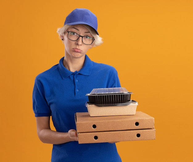 Молодая женщина-доставщик в синей форме и кепке в очках держит коробки для пиццы и продуктовые пакеты с грустным выражением лица над оранжевой стеной