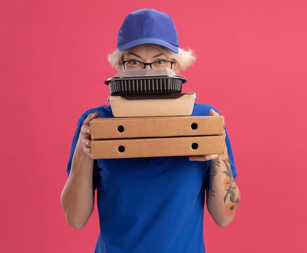 Молодая женщина-доставщик в синей форме и кепке в очках держит коробки для пиццы и продуктовые пакеты с серьезным лицом над розовой стеной