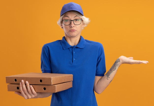 Молодая женщина-доставщик в синей форме и кепке в очках, держащая коробки для пиццы, путается с поднятой рукой, не имея ответа, над оранжевой стеной