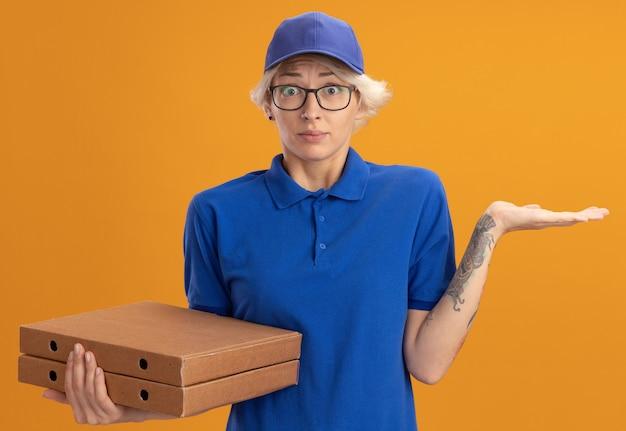 Молодая женщина-доставщик в синей форме и кепке в очках, держащая коробки для пиццы, путается с рукой, поднятой над оранжевой стеной