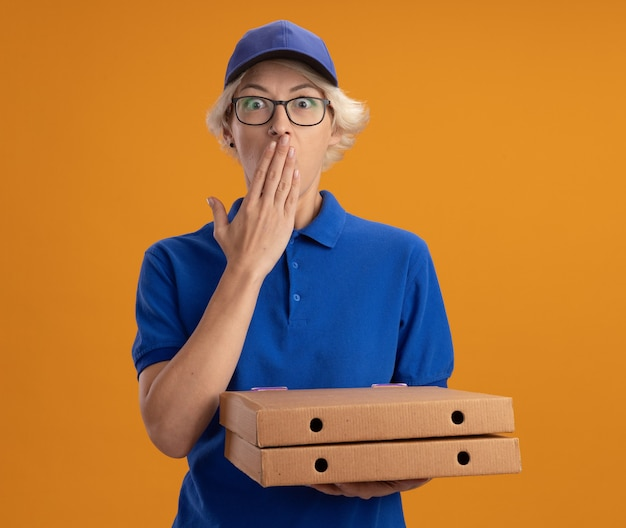 Молодая женщина-доставщик в синей форме и кепке в очках держит коробки с пиццей в шоке, прикрывая рот рукой над оранжевой стеной