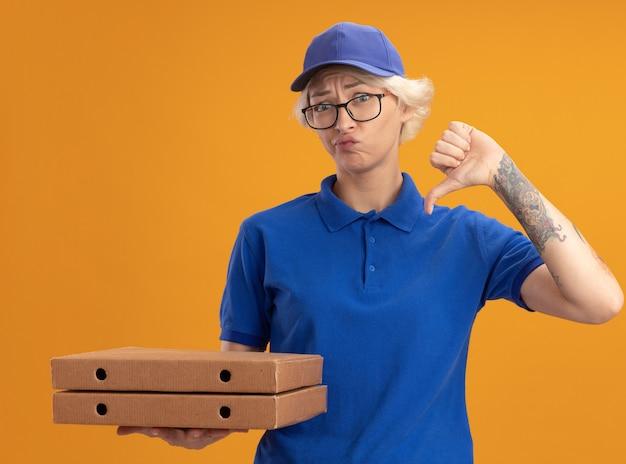 Молодая женщина-доставщик в синей форме и кепке в очках держит коробки с пиццей, недовольно показывает палец вниз над оранжевой стеной