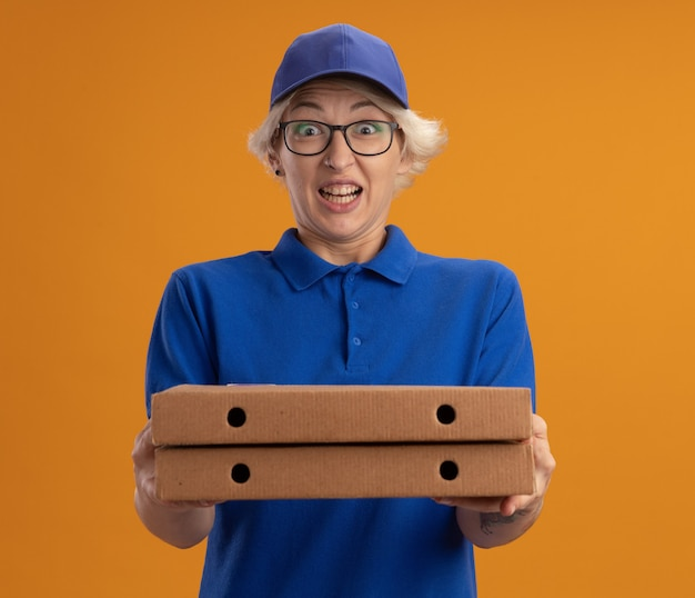 Молодая женщина-доставщик в синей форме и кепке в очках держит коробки для пиццы, взволнованные и счастливые над оранжевой стеной