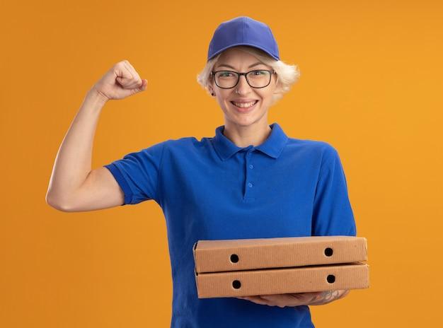 Молодая женщина-доставщик в синей форме и кепке в очках держит коробки с пиццей, счастливая и уверенная, сжимая кулак над оранжевой стеной