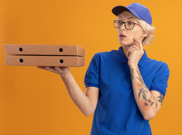 Молодая женщина-доставщик в синей форме и кепке в очках держит коробки с пиццей, озадаченная оранжевой стеной