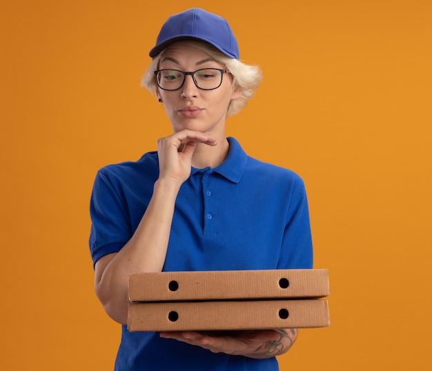 Молодая женщина-доставщик в синей форме и кепке в очках держит коробки для пиццы, задумчиво глядя в сторону над оранжевой стеной