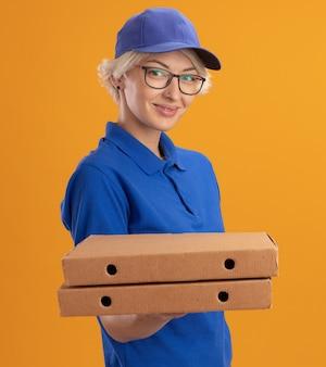Молодая женщина-доставщик в синей форме и кепке в очках держит коробки для пиццы, глядя на камеру, уверенно улыбаясь над оранжевой стеной