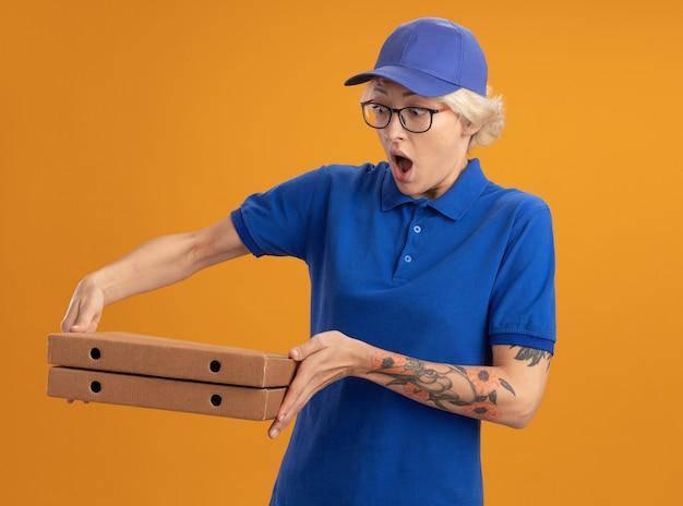 Молодая женщина-доставщик в синей форме и кепке в очках держит коробки для пиццы, глядя на них изумленно и удивленно над оранжевой стеной