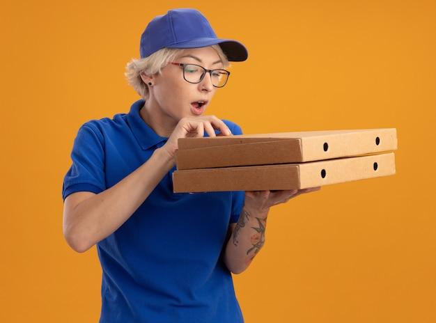 Молодая женщина-доставщик в синей форме и кепке в очках держит коробки с пиццей и заинтригованно смотрит на них над оранжевой стеной