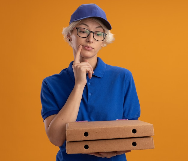 Молодая женщина-доставщик в синей форме и кепке в очках держит коробки для пиццы, глядя вниз с задумчивым выражением лица над оранжевой стеной