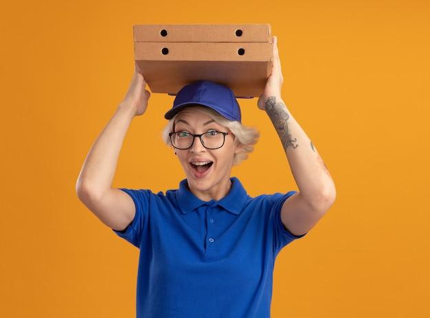 Молодая женщина-доставщик в синей форме и кепке в очках держит коробки с пиццей над головой, улыбаясь со счастливым лицом над оранжевой стеной