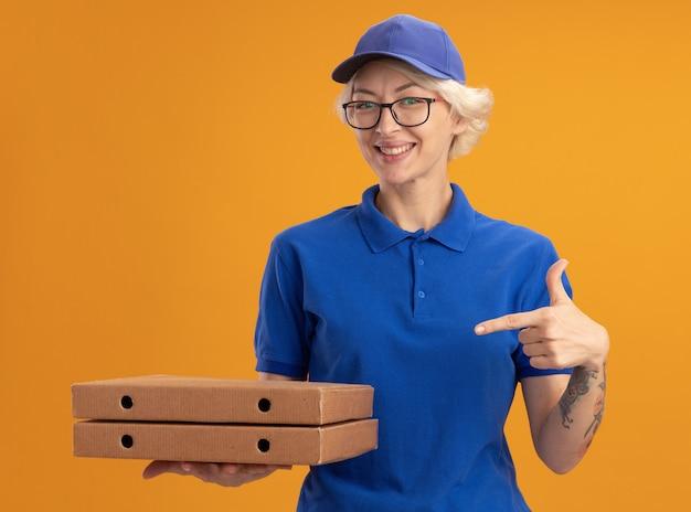 Молодая женщина-доставщик в синей форме и кепке в очках держит коробки с пиццей, указывая на них указательным пальцем, весело улыбаясь над оранжевой стеной