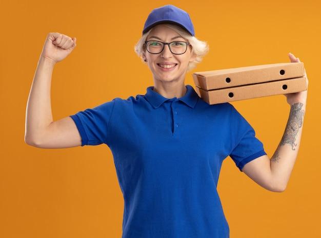 Молодая женщина-доставщик в синей форме и кепке в очках держит коробки для пиццы, поднимая кулак, счастливая и веселая над оранжевой стеной