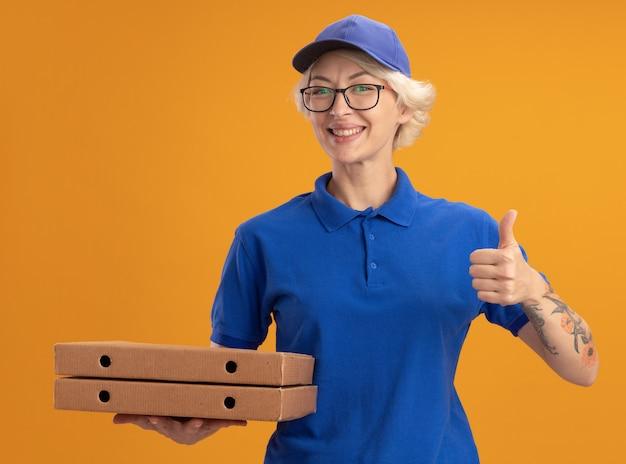 Молодая женщина-доставщик в синей форме и кепке в очках держит коробки для пиццы, показывая пальцы вверх, улыбаясь над оранжевой стеной