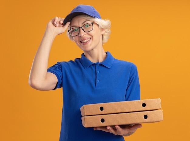 파란색 제복을 입은 젊은 배달 여자와 피자 상자를 들고 안경을 쓰고 모자를 쓰고 자신감이 오렌지 벽 위에 그녀의 모자를 고정 웃고
