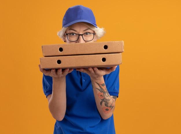 Молодая женщина-доставщик в синей форме и кепке в очках держит коробки для пиццы, лукаво улыбаясь над оранжевой стеной
