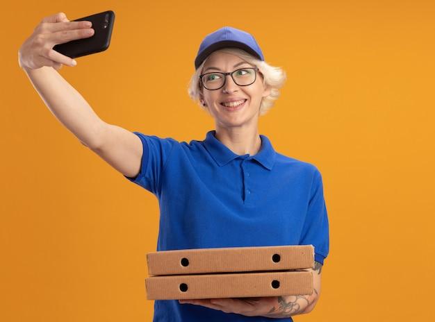 파란색 제복을 입은 젊은 배달 여자와 오렌지 벽 위에 웃는 셀카를하고 스마트 폰을 사용하여 피자 상자를 들고 안경을 쓰고 모자