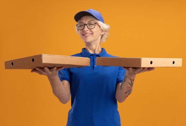 Молодая женщина-доставщик в синей форме и кепке в очках держит коробки для пиццы с большой улыбкой на лице над оранжевой стеной