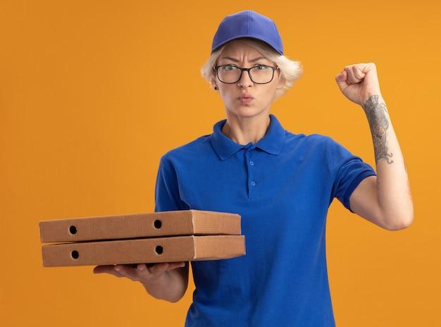 Молодая женщина-доставщик в синей форме и кепке в очках держит коробки для пиццы с серьезным лицом, поднимающим кулак над оранжевой стеной