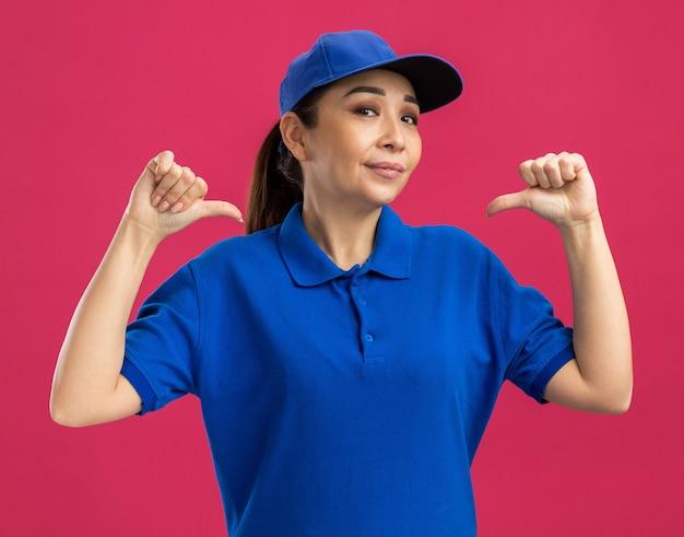 Молодая женщина-доставщик в синей форме и кепке с уверенным выражением лица показывает на себя большими пальцами, стоящими над розовой стеной
