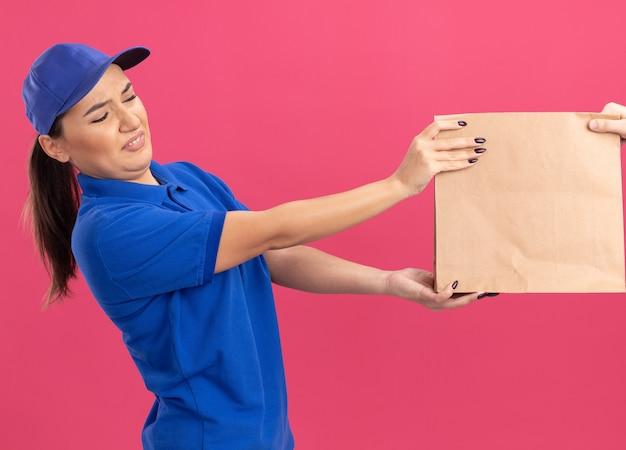 ピンクの壁の上に立っている紙のパッケージを受け取るうんざりした表情の青い制服とキャップの若い配達の女性