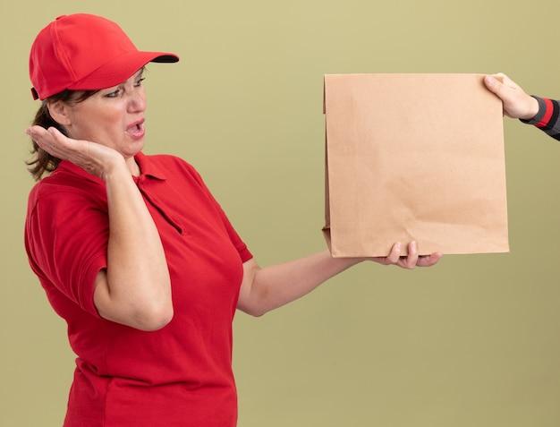 緑の壁の上に立っている紙のパッケージを受け取っている間興奮している赤い制服とキャップの若い配達の女性