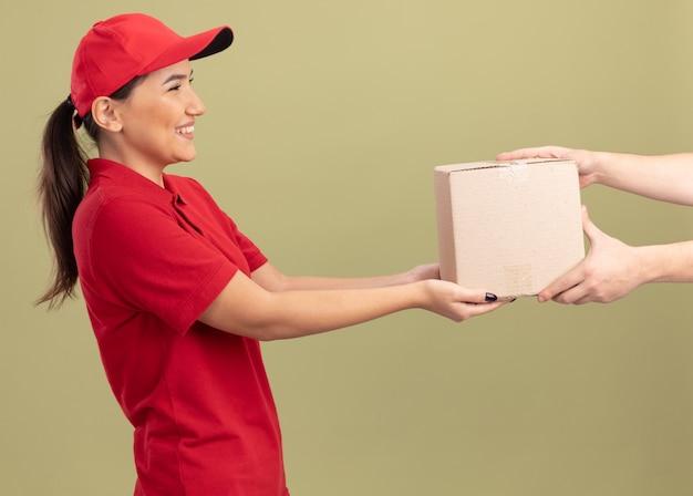 緑の壁の上に立ってフレンドリーな笑顔の顧客に段ボール箱を与える赤い制服とキャップの若い配達女性