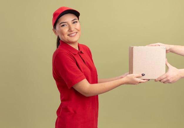 Молодая женщина-доставщик в красной форме и кепке дает картонную коробку клиенту, дружелюбно улыбаясь, стоя у зеленой стены