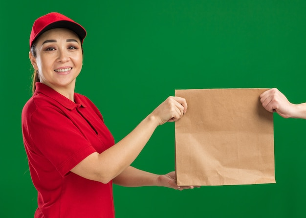 赤い制服を着た若い配達女性と、緑の壁の上に自信を持って立っている笑顔の顧客に紙のパッケージを与える帽子
