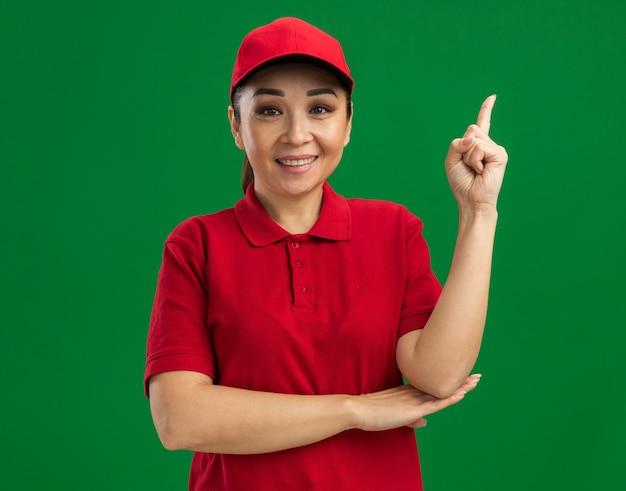 赤い制服を着た若い配達女性と帽子をかぶった幸せでポジティブな人差し指が緑の壁の上に自信を持って立って笑っている