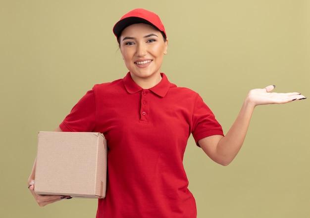 녹색 벽 위에 서있는 그녀의 손의 팔로 자신감을 제시 복사 공간을 미소 앞에보고 골판지 상자를 들고 빨간 유니폼과 모자 젊은 배달 여자