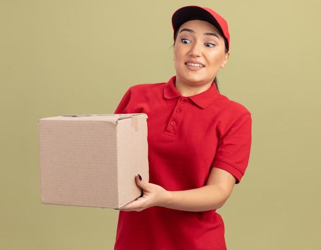 赤い制服を着た若い配達の女性とそれを見て幸せで驚きの緑の壁の上に立って段ボール箱を保持しているキャップ