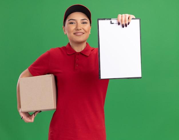 젊은 배달 여자 빨간색 유니폼과 모자 녹색 벽 위에 유쾌하게 서 웃 고 앞을보고 빈 페이지와 클립 보드를 보여주는 골 판지 상자를 들고