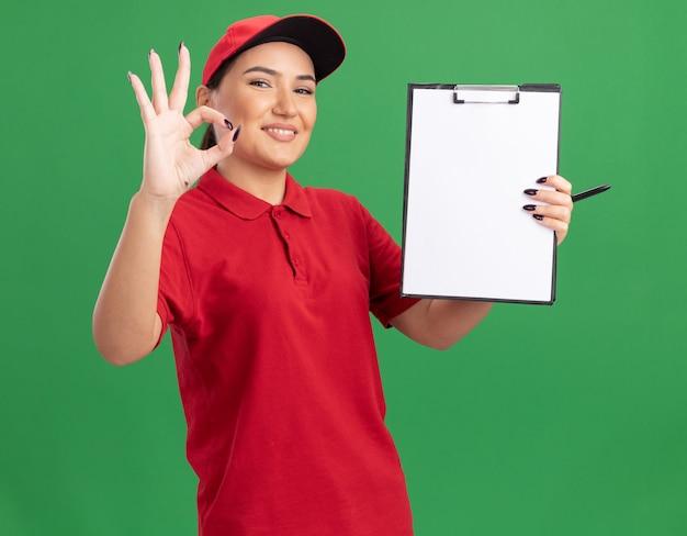 빨간색 유니폼과 모자를 들고 젊은 배달 여자 앞을보고 빈 페이지와 클립 보드를 들고 유쾌하게 녹색 벽 위에 서있는 확인 서명을 보여주는 미소