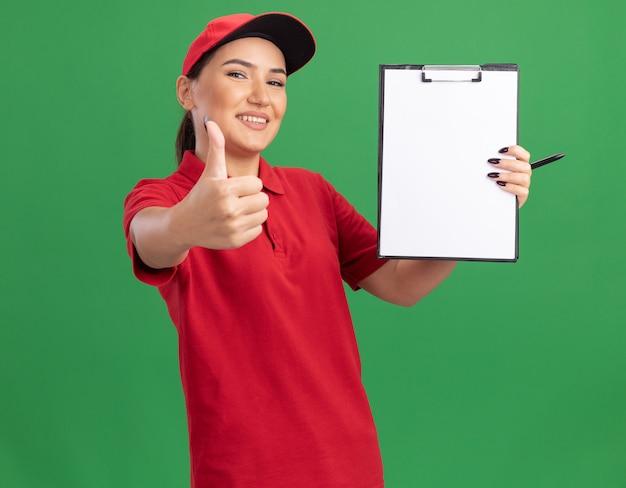 빨간색 제복을 입은 젊은 배달 여자와 녹색 벽 위에 서있는 엄지 손가락을 유쾌하게 보여주는 전면을보고 빈 페이지와 클립 보드를 들고 모자
