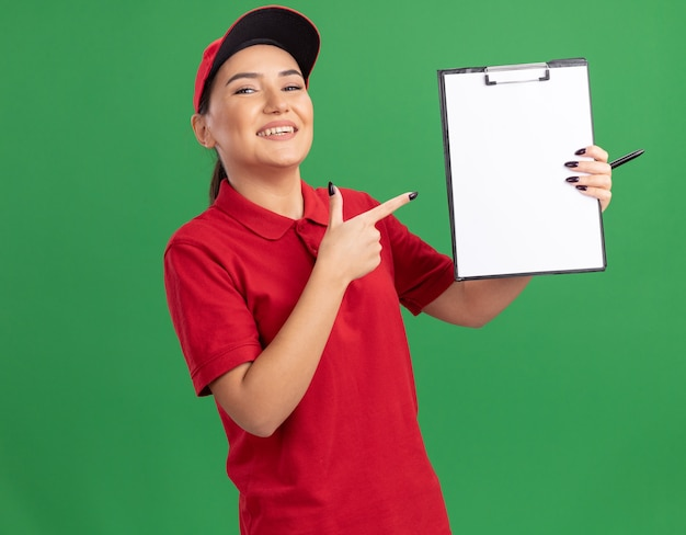 빨간색 유니폼과 모자를 들고 젊은 배달 여자 클립 보드에 검지 손가락으로 가리키는 빈 페이지가 녹색 벽 위에 유쾌하게 서 웃고 전면을보고