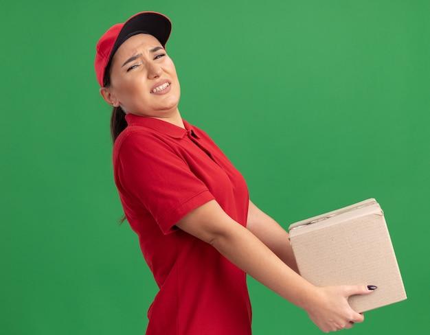 緑の壁の上に立っているイライラした表情で疲れているように見える重い段ボール箱を保持している赤い制服と帽子の若い配達の女性
