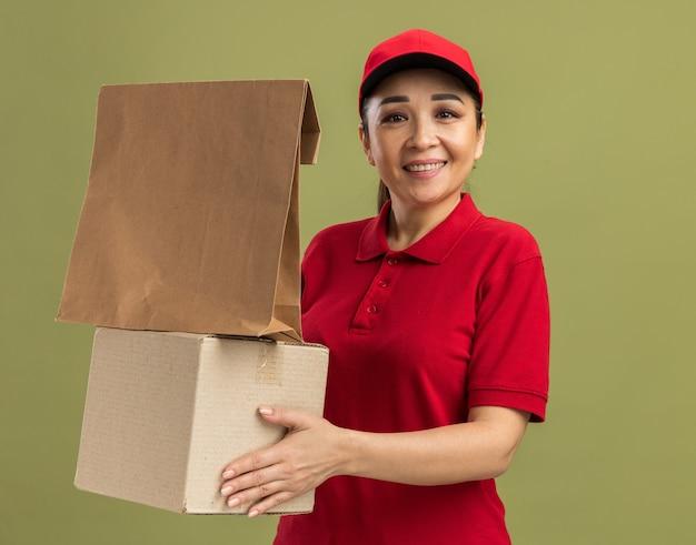 빨간색 유니폼과 모자 종이 패키지와 골판지 상자를 들고 행복하고 긍정적 인 녹색 벽 위에 서있는 젊은 배달 여자